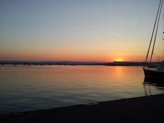 Il sole adagiato sulle contrafforti dei monti Climiti che accarezza coi suoi colori le acque del porto Grande