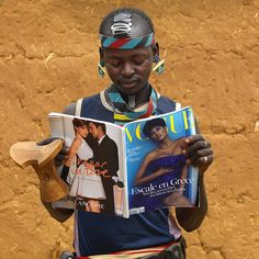 Tsemay warrior reading Vogue - Omo Ethiopia - photo by Eric Lafforgue