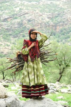 Faces of Iran. Carrying woods is not compatible with her beautiful costume-it does not look real. Is it for show?
