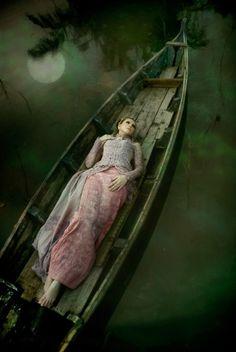 full moon reflection, dark waters, canoe, woman laying in boat, dark, creepy, strange, beautiful