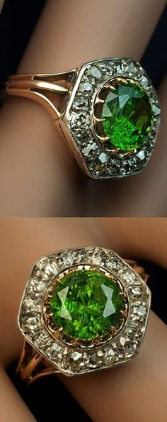 A Rare Almost 3 Carat Russian Demantoid and Diamond Ring made between 1908 and 1917 The silver topped 14K gold ring features a very large vivid grass green 2.84 ct Russian demantoid (8.55 x 5.45 mm) prong-set in gold within a hexagonal frame embellished with old cut diamonds (approximately 1.20 ct total weight). Marked with 56 zolotnik gold standard: