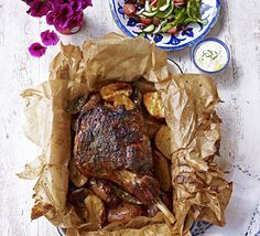 Seal a leg of lamb in a parcel then roast it long and slow with garlic, lemon and herbs, and potatoes to soak up the delicious juices. **GF