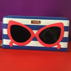 """Brand New Kate Spade Wallet Saffiano Leather with patent leather sunglasses design  14-karat light gold plated hardware custom woven lining zip around continental wallet 12 credit card slots, 3 billfolds, and zipper change pocket; exterior slide pocket 3.9""""h x 7.6""""w x 0.8""""d kate spade Bags Wallets"""