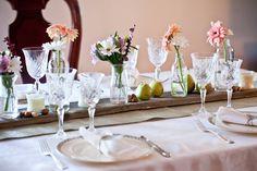 Tablecloth, burlap, wooden board, glass bottles, flowers.  Rustic & pretty.