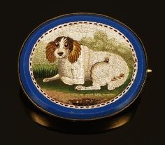 A mid Victorian gold and micro mosaic brooch, circa 1870, the central oval micro mosaic panel depicting a spaniel laying on grass, within a pale blue glass frame and gold brooch mount, 2.7cm long