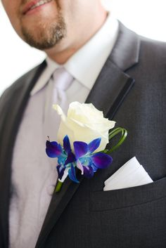 Groom Boutineer made of white rose and dyed blue purple dendrobium orchids with green accent. Purple wedding  Kayla & Derek Photo By Kirsten Smith Photography