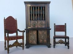 Rare Tynietoy Spanish Cabinet with two chairs. In some of the original Tynietoy catalogs, you will see photos of Spanish furniture. However, no catalog shows all the pieces! The high back Spanish chair on the left is shown as being part of the library set. It has brass finials and the edges are painted circles to resemble brass tacks. The center piece is the dining room china cabinet. The chair on the right is a bedroom chair. The chairs are painted wood to resemble leather.