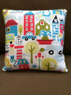 Colorful organic children's pillow with city full of buildings, trees, cars and cats