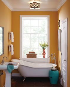 """designmeetstyle: """" A vibrant and cheery bathroom is balanced with classic white fixtures like this pedestal sink and claw foot tub. Centered at the window, the free standing tub creates a stunning..."""