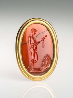 Red carnelian. Intaglio. Slightly convex front, convex back; set in modern mount. Theseus is depicted nude, in profile right. He stands with his weight on his right leg and his left leg is relaxed, with the knee slightly bent. He bends his head to study a sheathed sword clasped before him with both hands; the right grips the bottom of the scabbard, while the left reaches out to grasp the scabbard below the hilt of the sword, near the strap. A shield lies on the ground before him, decorated…