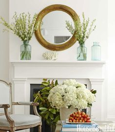 In the living room, flowers in antique pickle jars and a rustic coffee table from Homer offset the formality of the mantel. Morgan likes the elegant simplicity of using only one type of flower in each arrangement.   - HouseBeautiful.com