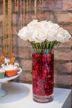 Love this idea of adding cranberries to a clear vase full of white flowers for a hholiday theme!