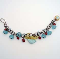 https://flic.kr/p/5CSLpz | The Bird's the Word | Charm bracelet on Vintaj Brass Co. cable chain Bird and Nest charms- Earthenwood Studio Handforged brass clasp Frosted Recycled coke glass beads Lampwork glass rings Red Buri seeds Yellow Opal wheels Bronze glass seed beads