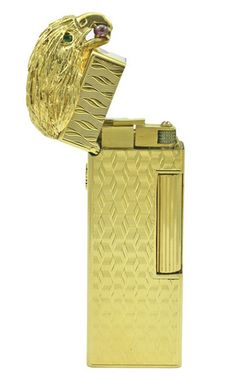 DUNHILL Gold Cigarette Lighter, Extraordinary 18K gold cigarette lighter, made and signed by Dunhill. Figural eagle's head perched atop the lighter. Beautiful gold textured life- like feathers; bright faceted emerald eyes; a large cabochon ruby in its beak. This is gorgeous and exceptional.