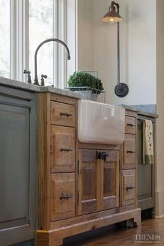 A white apron sink set into a weathered wood base is given a fresh, current look with adjacent painted cabinets.