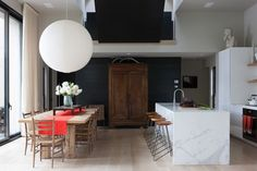 A dramatic yet minimal kitchen and dining area in a home in Copake, New York, designed by Meyer Davis. | Lonny