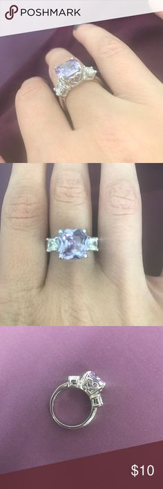 Light purple ring This lovely princess cut cubic zirconia ring is light purple with two clear stones. It has a total of 4 hearts that surrounds the setting. It is rhodium coated and a size 6. NWOT!!!!!!! Jewelry Rings