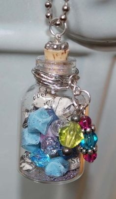 bottle necklace is filled with tiny little lucky origami stars. Some of the stars were made from a rescued Alice In Wonderland book, the others were made from vellum and specialty paper.