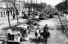 Two Red Army riders pass among the remnants of a German column in the streets of liberated Odessa, Ukraine, 1944.