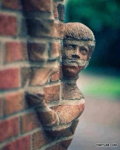 Emerging from the wall. Uses surrounding objects to create an interesting sculpture of a boy.