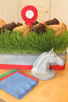 The Polohouse. Chocolate and peanut butter horse head lollipops raced on a bed of wheat grass