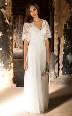 Wedding Dress of embroidered tulle with bell sleeves, and a v-neck. Satin button back closure.  Empire waist and skirt of cotton netting.