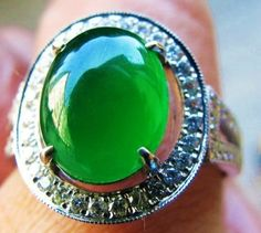 A imperial green jadeite ring set in a circle of diamonds