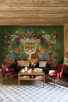 Mural of highly stylized floral design in a traditional Indian format highlights the majestic male tiger that serves as its focal point. Dark green background, natural wood ceiling and table, and solid leather chairs help balance the dramatic accent wall. Bright, traditional geometric needlework in the throw pillows and afghan help tie the room together.
