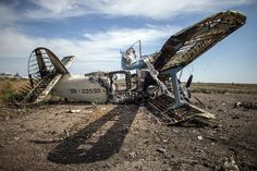 15. September: Auf dem zerstörten Flughafen von Lugansk in der Ostukraine verrottet ein ausgebranntes Flugzeug | September 15th 2014: At Lughansk airport in Ukraine a burned-out aircraft starts rotting on the field. Another Antonov in the background looks still intact