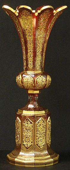 "This is a truly exceptional example of a Moser Bohemian art glass vase. The vase is a translucent cranberry glass made from 8 panels in a cylindrical array, flaring out in the center, then narrowing at the waist and flaring out againtowards the base. Each panel comes to a point with beveled edge.There are copious amounts of raised gilt enamel tracing intricate geometric patterns that cover each panel, a characteristic Moser trademark. Measures: 16"" Tall X 6 7/8"" Wide"