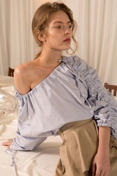 The Luanda in Airy Blue, featuring wide square neckline with gussets at shoulders, long bell sleeves with optional drawstring seam and tie details at cuff and hem for adjustable shirring and cinched by the elasticated smocked trims.