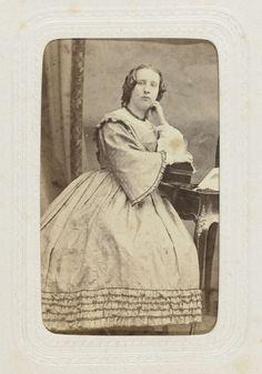 Wegner & Mottu | Studioportret van een vrouw met pijpenkrullen en bolle jurk, Wegner & Mottu, c. 1863 - c. 1870 |