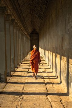 A Buddhist monk walk along the left wall of Angkor Wat temple, Siem Reap Kingdom of Cambodia.