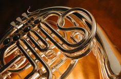 Close-up view of a French horn, showing its gleaming surfaces and sinuous design.