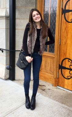 A college student from Franklin and Marshall College shows off her street style, wearing skinny jeans, ankle boots, and a faux fur vest.