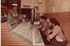 """(From DigiKiller Records) """"mixing in the Harry J control room!   standing: bass player Derrick Barnett. seated at board, in blue shirt, engineer Barry Murray. with beard, vocalist Clive Matthews."""""""