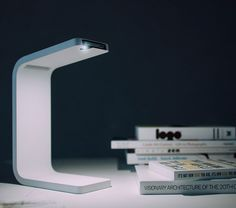 """Ukrainian industrial designer Ivan Zhurba's iPhone Lamp sources its light from the flashlight feature of an iPhone, which would be slotted into the thin """"arm"""" of the minimalist apparatus. The design also allows for a charging cable while the iPhone is in use and, as Designboom details, includes an """"acoustic tunnel that amplifies the sound coming from the speaker of the iPhone."""""""