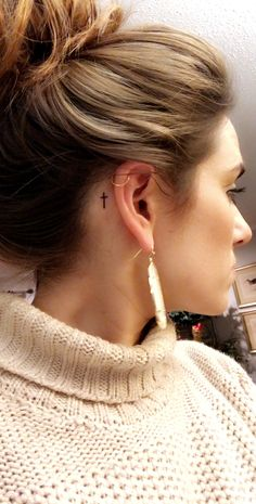Small cross tattoo behind the ear