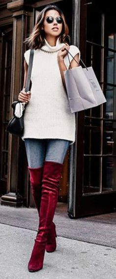 Annabelle Fleur wears crimson over the knee Stuart Weitzman boots, jeans, and a knitted vest.