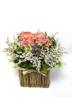 This contemporary floral arrangement is ready to add some fall flair to your table or desk. It starts with 5 peachy-pink roses that are surrounded by german statice, puple oregano blooms and boxwood, and is finished with natural green moss flowing out from under the statice. These lovely flowers are seated in square twig container that measures 5 wide by 5 high. The overall finished arrangement measures approximately 8 high by 9 1/2 wide (tip-to-tip). A lovely arrangement that is contemp...