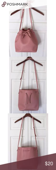 pink vegan leather drawstring bucket bag Medium size bucket bag is made from vegan leather and has a drawstring closure. Exterior is a pale, flesh pink while interior is a bright, rich rosy pink. Only worn once and looks like new. Very cool bag, but my color so I would like to find it a good home. Bags Shoulder Bags