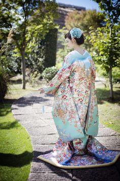 打掛『加賀調懸崖椿菊』、掛下『ブルーぼかし花ふぶき』空のように鮮やかな青色から濃い青色へのグラデーション。椿の赤や御所車が全体を引き締め、織物の重厚さと相まって格調高い爽やかな一着。