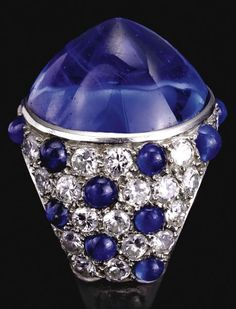 An Art Deco cabochon sapphire and diamond ring, probably by Cartier, circa 1930. The circular cabochon sapphire collet-set to a surround of circular-cut diamonds decorated with cabochon sapphires, mounted in platinum, French assay and indistinct maker's marks.