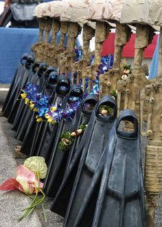Five pairs UDT Duckfeet (fins) have a lei draped over them, representing the five fallen SEALs from SDVT-1 in Hawaii.