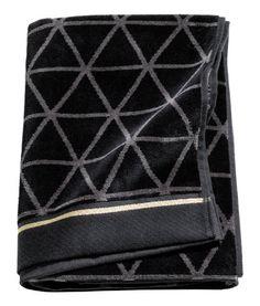 Svart/Guld. En jacquardvävd badhandduk i bomullskvalitet med framsida i velour och baksida i frotté. Handduken har bandkantade kortsidor med broderad rand
