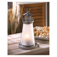 Brighten your evening with a cheery seaside glow; just add a votive inside this miniature lighthouse and enjoy the ambiance! Candle not included. Iron & glass.
