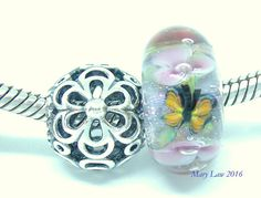 This OOAK Glaslight Studio Artisan lampwork bead has pink flowers with bubble centers alternating with a butterfly and ladybug over green and gold vines and a sparkling dichroic base. Encased in crystal clear for a magnifying effect. Buyer of this bead will see alot of beautiful sparkle not captured in these pictures. The Pandora charm measures 11.5 by 10.5 mm. The Glasslight Bead measures 16mm by 8mm and will fit on the Pandora bracelet. Both beads will fit on the pandora bracelets. Photo…