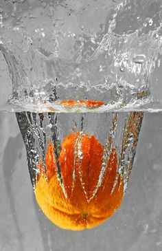 Orange dropping into water