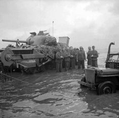 German prisoners, up to their knees in the sea, wait for collection in the shadow of a disabled Sherman Crab flail tank. June 6, 1944.