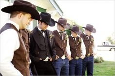 The groomsmen in coral vests and jeans with white cowboy hats